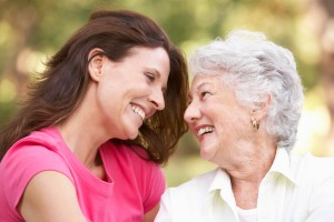 Senior Woman With Adult Daughter In Park Smiling